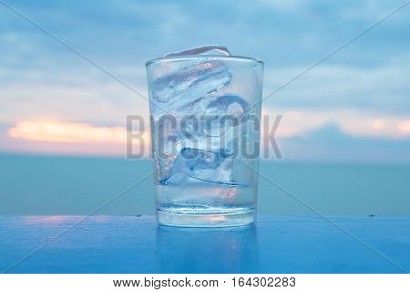 A glass with ice and sunset at sea with quiet feel or blue tone on the background