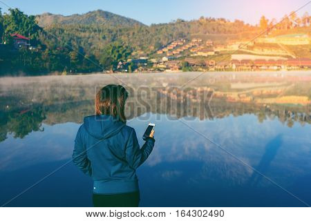 Beautiful asian woman used smartphone and making selfie outdoors with Sunrise scence of Ban Rak thai village in Mae Hong Son veiw of mountains under mist near Chiang Mai Thailand with vintage tone