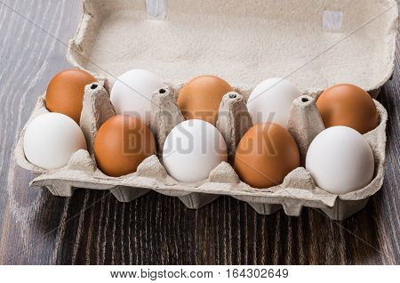Opened Carton With Eggs White And Brown On Table