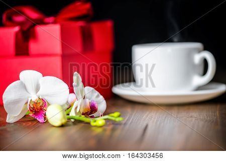 Greeting Red Box With Bow, Orchid Flower, Phalaenopsis And Cap Of Tea On Wooden Background, Close Up