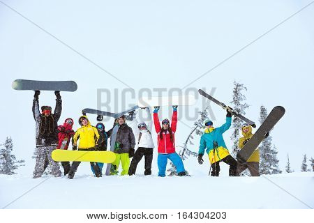 Group of happy friends skiers and snowboarders posing at off-piste slope