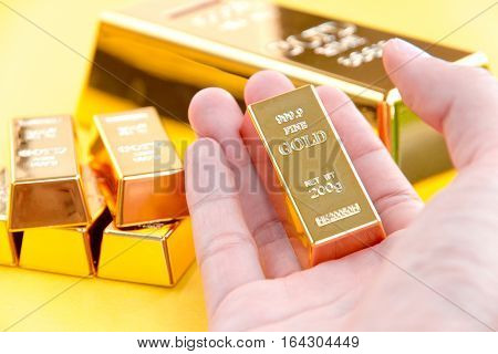 close up image of Hand hold gold bars