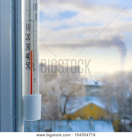 Cold winter weather. Outdoor thermometer on a window shows a minus thirty degrees Celsius. Low temperatures under zero