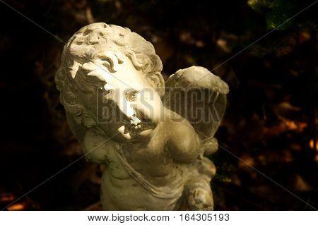 cupid cement sculpture god of love with dark garden background