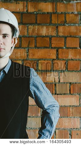 Portrait of the half face young engineer on the brick background
