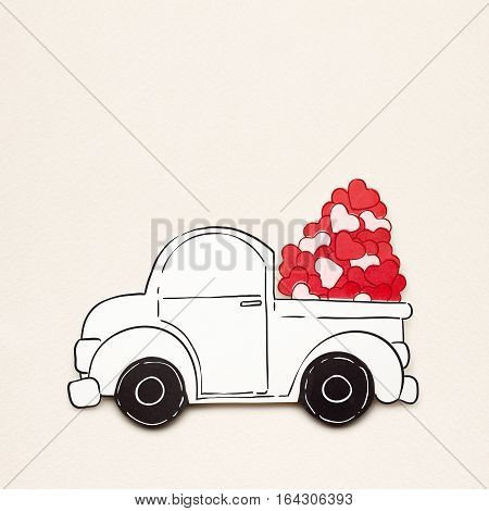 Creative valentines concept photo of paper car with hearts on grey background.