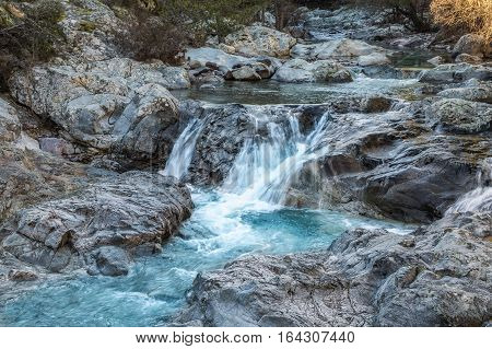 Icy water of the Tartagine river flowing over rocks and boulders in the mountains of the Balagne region of Corsica