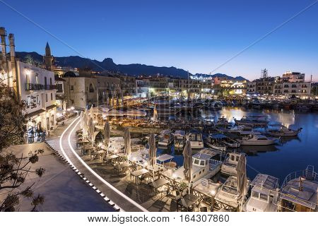 KYRENIA (GIRNE), NORTH CYPRUS - DECEMBER 19, 2016: Scenic night view of Kyrenia harbour with mountains on background. Kyrenia (Girne) harbour is one of the most popular tourist attractions in Cyprus.