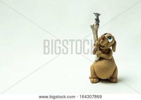 The dog holds a bone on which there is a mouse photographed on a light background