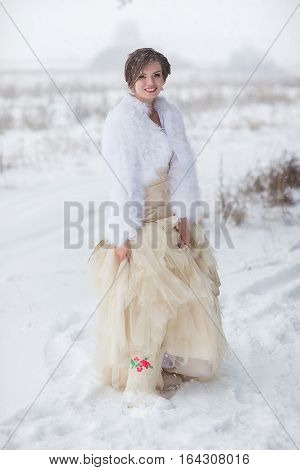 Bride in wool boots in winter forest in the snow