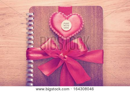 notebook wrapped with red ribbon red felt hearts with Made With Love medal on top in vintage pink color tone all on wooden table good for valentine or special occasion