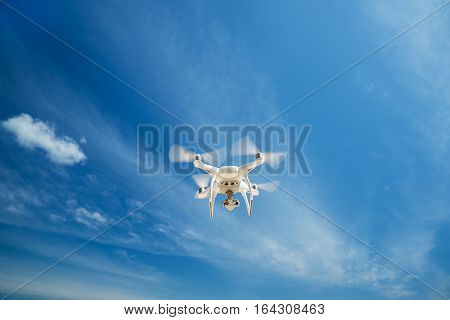 quadrocopter flight from digital camera. white drone hovering in a bright blue sky. New technology in the aero photo shooting.