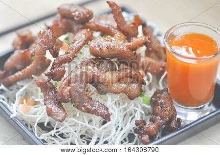 fried pork with fried noodle and chili sauce dish (Thai food)