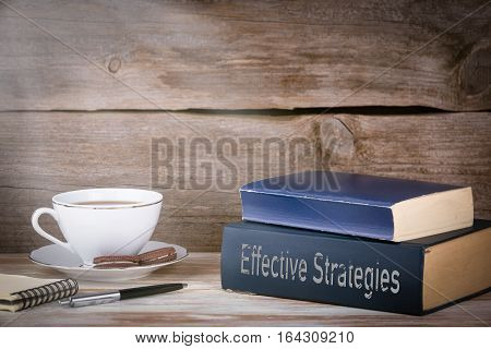 Effective Strategies. Stack of books on wooden desk.