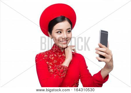 Portrait of a beautiful Asian woman on traditional festival costume Ao Dai taking selfie photo by smartphone