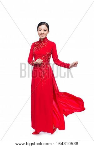 Full length of a beautiful Asian woman on traditional festival costume Ao Dai. Tet holiday. Lunar New Year.