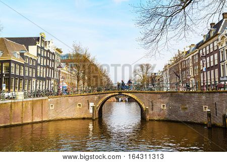 Amsterdam, Netherlands - March 31, 2016: Traditional old buildings, canal and bridge view in Amsterdam, the Netherlands