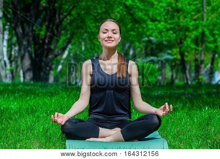 Beautiful young athlete sits in a lotus position on the mat in the nature. Healthy lifestyle.