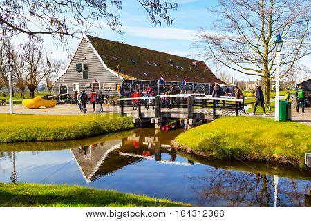 Zaanse schans, Netherlands - April 1, 2016: Wooden shoes, clogs or klompens museum in Holland, people around