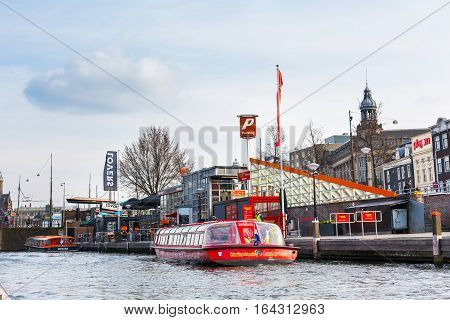 Amsterdam, Netherlands - April 1, 2016: Canal and cruise boat in Amsterdam, the Netherlands