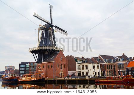 Haarlem, Netherlands - April 2, 2016: Picturesque morning landscape with the windmill and traditional houses, Haarlem, Holland