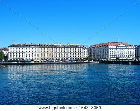 GENEVA, SWITZERLAND, EUROPE on JULY 2016: White representative hotel buildings on city promenade at Rhone River landscape near swiss alpine Leman Lake with clear blue sky in warm sunny summer day.
