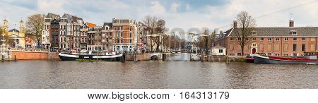 Amsterdam, Netherlands - April 2, 2016: Traditional old buildings, canal and bridge panoramic view in Amsterdam, the Netherlands