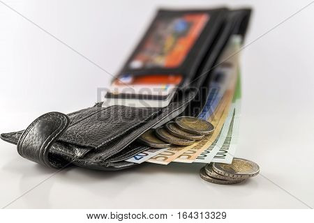 Leather men's open wallet with euro banknotes bills coins and credit card inside isolated on white background.