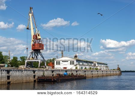 Warehouses and port crane in cargo river port of Nizhny Novgorod on the Strelka. View from the Oka River. 2016