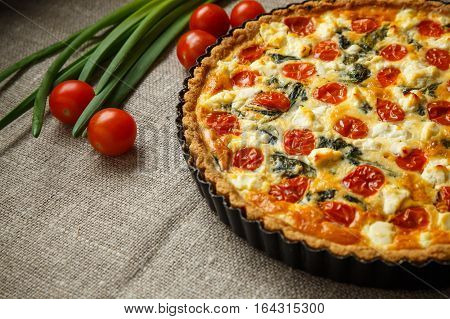 Vegetarian homemade pie, Quiche with tomatoes, spinach and feta cheese