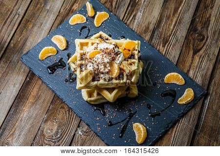 Photo of several Belgian waffles with chocolate, tangerines and ice-cream on blackboard