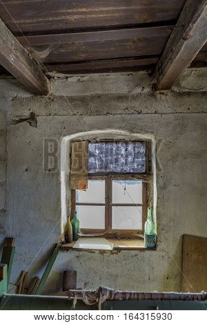 Room in an old abandoned house with grunge wall and wooden ceiling. Old window frame in an abandoned rural house.