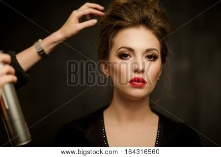 Stylist corrects hair of beautiful woman in studio