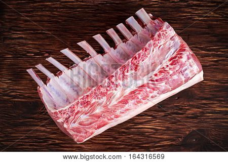 Fresh Raw French whole rack of pork loin with ribs on wooden board
