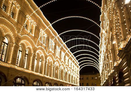City buildings with burning festoons at night in Christmas