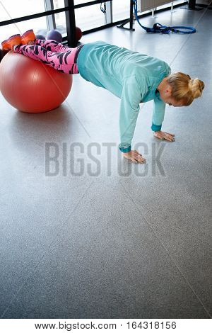 Photo of sportswoman engaged in fitness on ball in gym