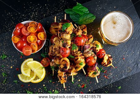 Chicken skewers marinated in turmeric yogurt served with lemon and mint.