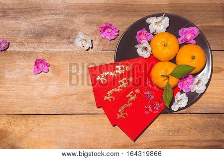 "Mandarin oranges and Lunar New Year with text ""Happy New Year"" on red pocket. Tet Holiday concept. Text mean Lucky and Happiness."
