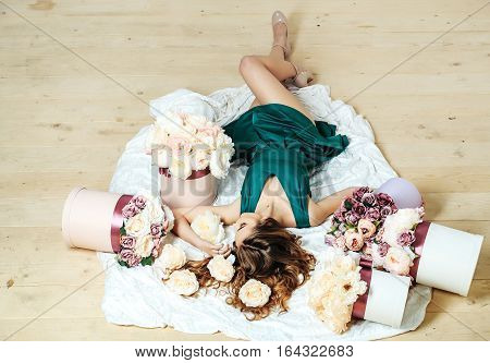 Sexy young pretty woman or cute girl with long hair in green dress laying on white bedsheet among lilac rose and peony flowers on wooden floor