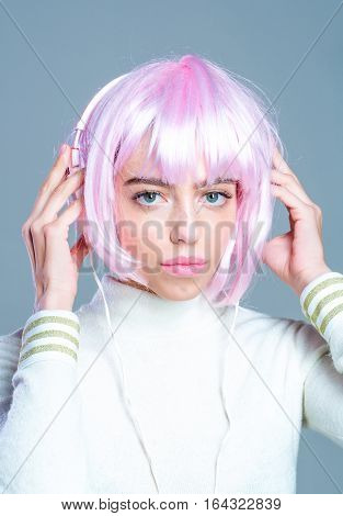 young pretty woman or cute sexy girl with pink glamour hair wig in fashionable shirt poses on grey background with music headset