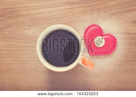 felt heart with Made With Love button and cup of coffee on wooded table good for valentine or special occasion