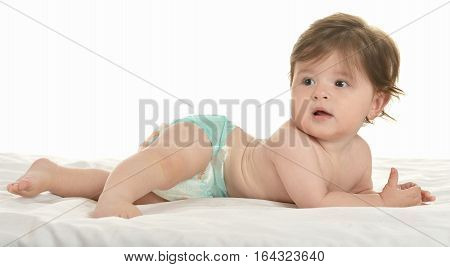 Adorable baby girl lying in pampers on a white background