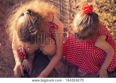 Two little sisters play with sand in park on a sunny summer day. Cute little girls at sunset. Soft focus top view