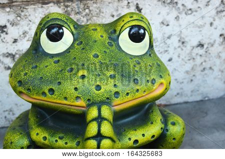 Cute green praying frog figurine gazing upwards