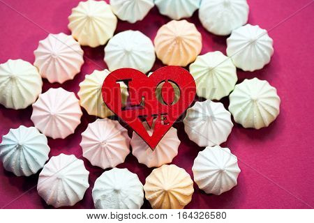 Pastel colors meringues with wooden figure of red heart on magenta background