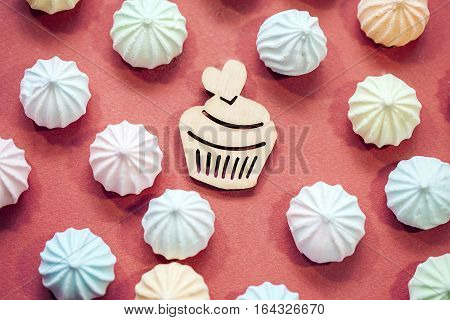 meringues in pastel colors with wooden figure of cupcake on red background