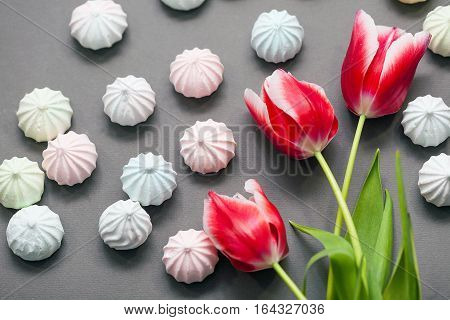 meringues in pastel colors with three red tulips on grey background. St Valentines's Day
