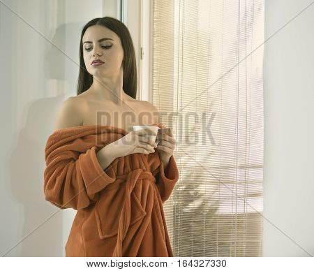 Beautiful half-naked girl with a cup of coffee