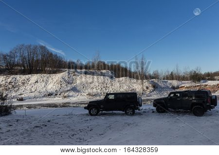 The river Tosno, Leningrad oblast, Russia - January 07, 2017, Hammer H3 and Jeep Wrangler Jk on the shore of the river, the Hummer H3 is a compact SUV produced by GM