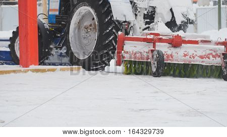 Tractor plowing snow on street, close up, telephoto